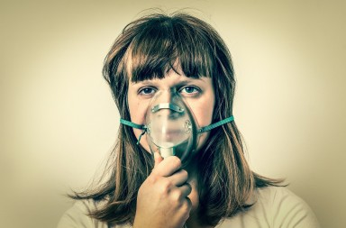 Diseased female patient with oxygen mask breathes oxygen in hospital - retro style